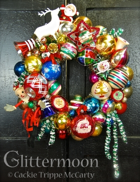 "A very Merry Christmas to all with this joyful, multi-colored wreath. Featuring a wonderful bendy Santa (he still had his original price tag from Blum's department store) on the left, a white reindeer on top next to a jolly little Santa, and tons of fabulous vintage ornaments. Trimmed out with old foil garland for extra spice. Approx. 17"" diameter. $195 ** SOLD **"