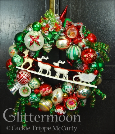 """A traditional Christmas color scheme of red, green, and white with a marvelous old plastic Santa and his reindeer crossing a dazzling ornament """"sky"""". Topped with a fab corsage and a gorgeous jumbo Poland ball. Plus so many other treasures! Approx. 20"""" diameter. $250. ** SOLD **"""