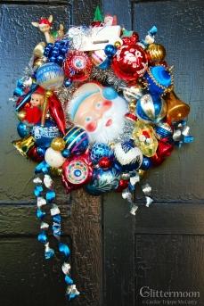 "SANTA BLUE A petite wreath (approx. 14"" diameter) in festive colors. Featuring a darling Santa face in the center. $125 ** SOLD **"