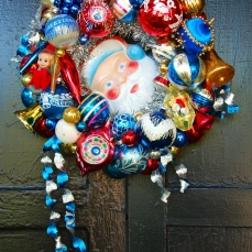 "SANTA BLUE A petite wreath (approx. 14"" diameter) in festive colors. Featuring a darling Santa face in the center. $125 ** SOLD **"