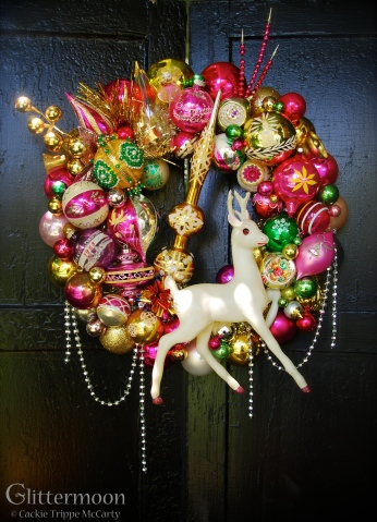 """HOT FLASH. Hot, poppy colors abound on this wreath, featuring a rare, huge (13"""" tall) celluloid deer and a gold topper as the focal points. 20"""" diameter $295 SOLD"""