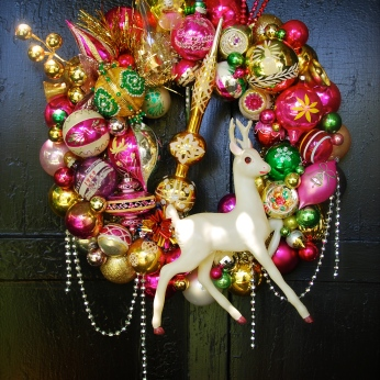 "HOT FLASH. Hot, poppy colors abound on this wreath, featuring a rare, huge (13"" tall) celluloid deer and a gold topper as the focal points. 20"" diameter $295 SOLD"
