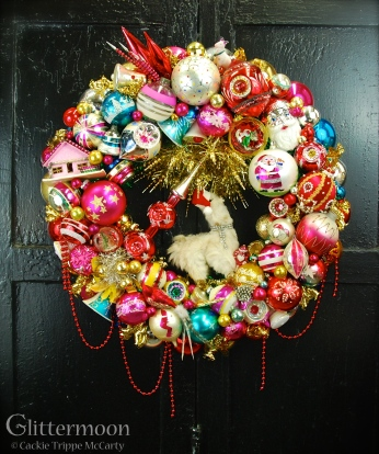"""The Lama Wreath, made especially to hang in the Beekamn 1802 Mercantile, Sharon Springs, NY. The largest wreath I have made to date and just loaded with all kinds of fab goodies; with a miniature Polka Spot (the llama) dress in her holiday finery of rhinestones and a Santa hat. About 27"""" diamater $525 *SOLD*"""