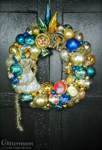 "Angel Blue: A lovely German wax angel is the centerpiece for this angelic wreath. Also featuring a Fontanini cherub, a Jewelbrite diorama, and other Nativity themed treasures. Approx. 20"" - $275 * SOLD *"